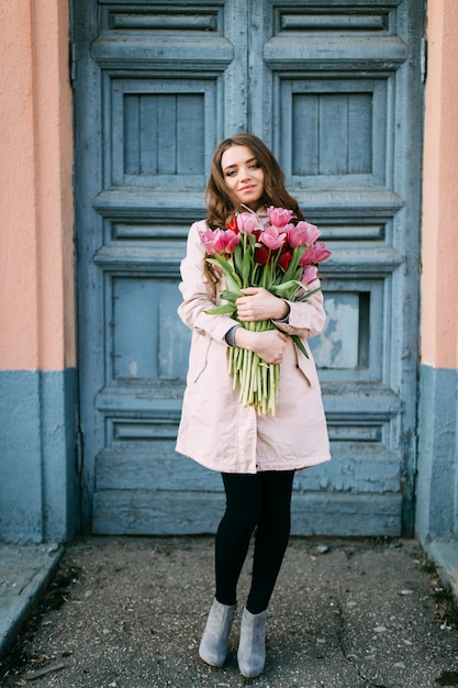 Lovely smiling brunette woman standing in front of old  door with a bouquet of fresh tulips. Premium Photo