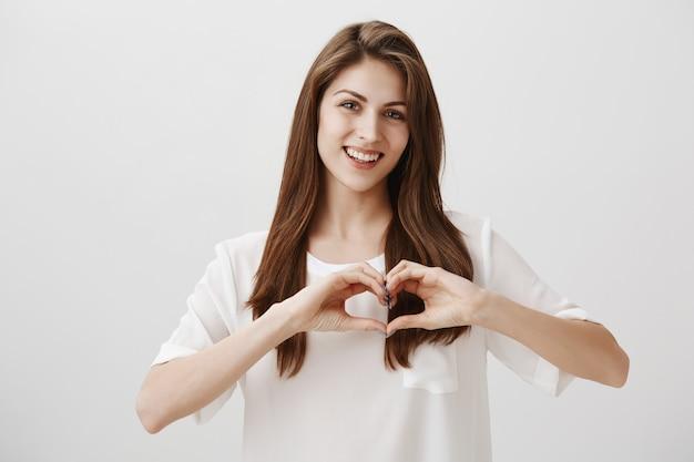 Прекрасная улыбающаяся счастливая женщина, показывающая жест сердца Бесплатные Фотографии