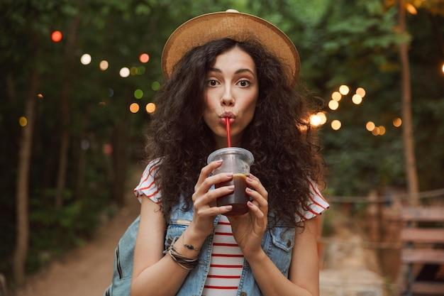 Lovely summer woman wearing straw hat, looking at you while drinking beverage from plastic cup during rest in green park with colorful lamps Premium Photo