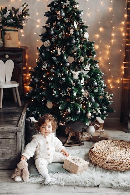 봉제 애완 동물과 크리스마스 트리 근처 카펫에 앉아 선물을 가진 사랑스러운 유아 무료 사진