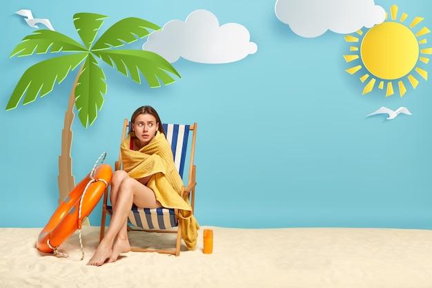 사랑스러운 여자는 바다에서 수영 한 후 추위를 느끼고 야자수 근처의 갑판 의자에 앉아 있습니다. 무료 사진