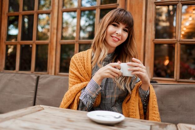 Bella donna ha una pausa caffè in un accogliente bar con interni in legno, parlando al telefono cellulare. tenendo la tazza di cappuccino caldo. stagione invernale. indossare abiti eleganti e plaid giallo. Foto Gratuite