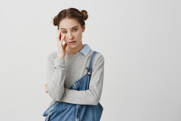 誰かが彼女の頭を手で持っていることにうんざりしているイライラした表情でポーズをとって素敵な女性。退屈な興味のない話を聞くのに飽きたデニムのオーバーオールを着ている少女。感情の概念 無料写真