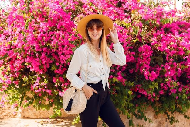 Прекрасная женщина, стоя на розовых цветках, соломенной шляпе и повседневной одежде. Бесплатные Фотографии