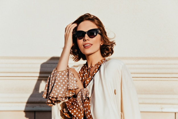 Lovely woman in vintage outfit expressing interest. outdoor shot of glamorous happy girl in sunglasses. Free Photo
