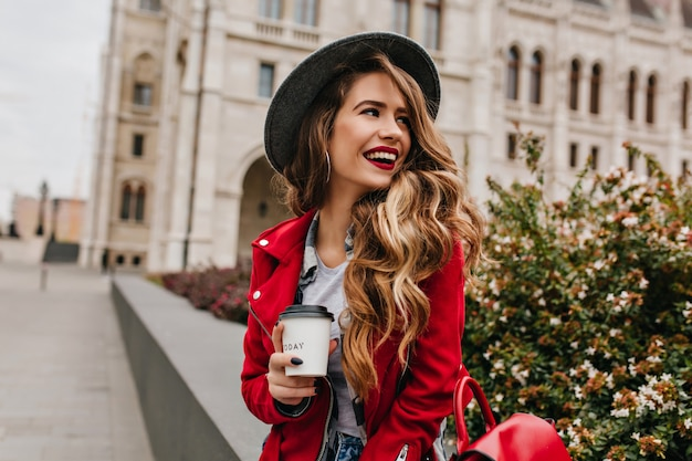 Lovely woman with elegant wavy hairstyle looking away while drinking coffee on the street Free Photo