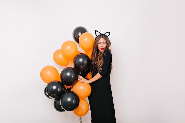 Милая женщина с воздушными шарами хэллоуина позирует с удовольствием на белой стене Бесплатные Фотографии