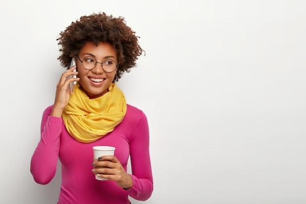 사랑스러운 젊은 아프리카 계 미국인 여성은 쾌활한 표정을 가지고 있으며, 전화 통화를하고, 테이크 아웃 커피를 마시고, 기쁜 표현을하고, 투명한 둥근 안경, 노란색 스카프 및 분홍색 터틀넥을 착용합니다. 무료 사진