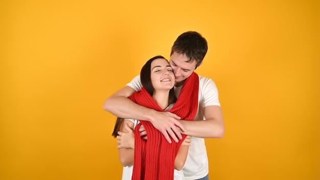 Прекрасная молодая пара обниматься. портрет счастливой молодой пары с красным теплым шарфом перед желтым фоном. празднование дня святого валентина. Premium Фотографии