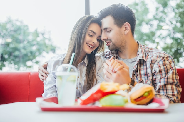 Lovely young couple in the modern fast food restaurant hugging together Premium Photo