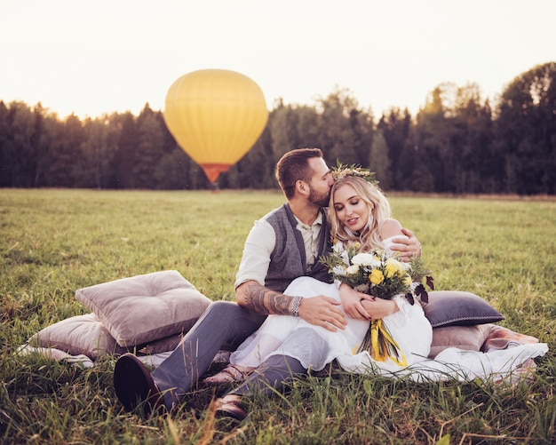 Lovely young couple in wedding dresses in bohho style, on a field with a balloon Premium Photo