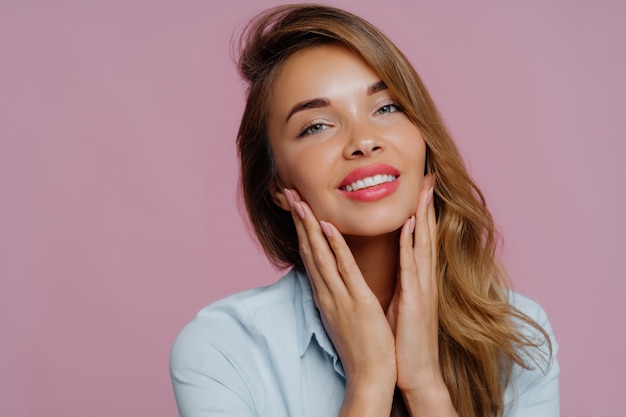 Lovely young female model touches gently chin with both hands, smiles gently, has tender look Premium Photo