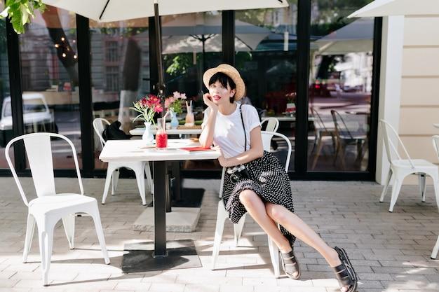 Милая барышня в летней шляпе отдыхает в летнем кафе, подперев лицо рукой и ожидая друга Бесплатные Фотографии
