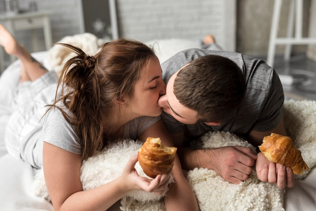Lovely young man and woman kissing in bed Free Photo