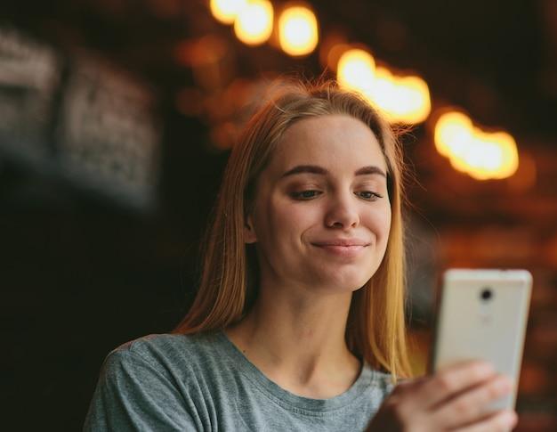 Прекрасная молодая женщина в кафе или ресторане держать смартфон в руке и смотреть на это с улыбкой. веселый счастливый женский человек с использованием современных технологий. Premium Фотографии
