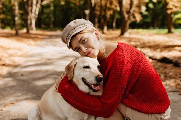 秋の公園で一緒にラブラドールと一緒に座っている素敵な軽い帽子と赤いセーターの素敵な若い女性。かなり金髪と落ち葉の間に座っている彼女の犬。 無料写真