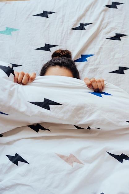 Прекрасная молодая женщина лежит в постели, покрытой одеялом Бесплатные Фотографии