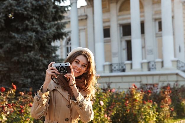フォトカメラを使用して、屋外を歩くコートを着て素敵な若い女性 Premium写真