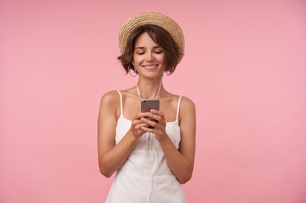 彼女の手で携帯電話を保持し、画面上で元気に見て、イヤホンで楽しいビデオを見て、孤立した短い茶色の髪の素敵な若い女性 無料写真