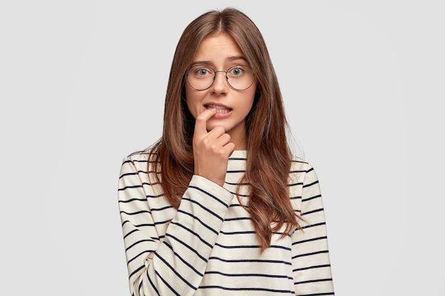 思いやりのある表情の素敵な若い女性は、縞模様のセーターを着て、丸い眼鏡をかけ、白い壁にポーズをとって、指を噛みます。物思いにふける心配の女子学生が何かを考える 無料写真