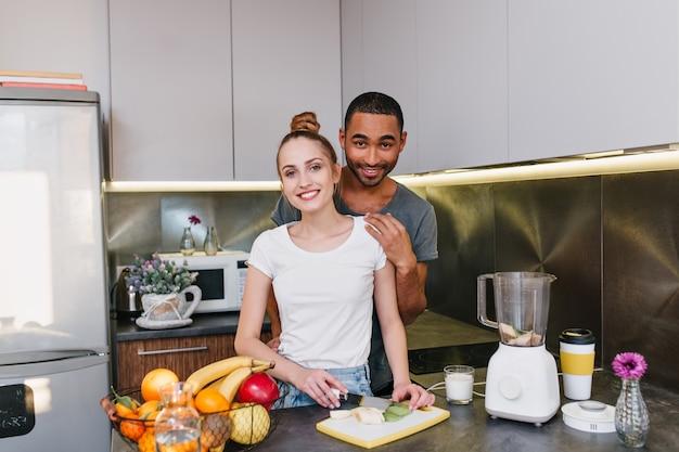 Влюбленные вместе готовят на кухне. девушка со светлыми волосами режет фрукты. пара в футболках с радостными лицами проводят время вместе дома. Бесплатные Фотографии