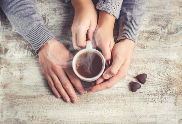 Lovers holding together a cup of tea. selective focus. Premium Photo