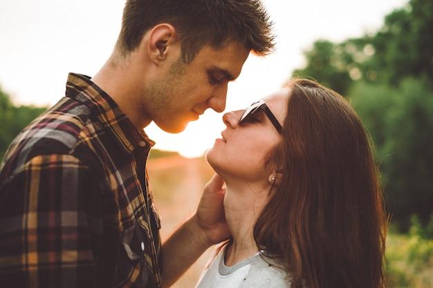 Loving boyfriend kisses his girlfriend, looking into his eyes, sunset, outdoor, sun rays Premium Photo