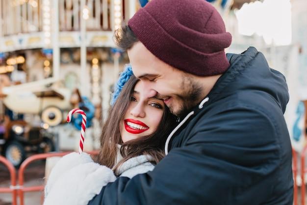 Coppia di innamorati che abbracciano nel parco di divertimenti nel fine settimana invernale. felice ragazza dai capelli neri che celebra il natale con il fidanzato e in posa davanti alla giostra in una giornata fredda. Foto Gratuite