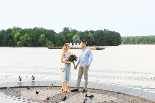 A loving couple a guy and a girl hold hands and stand of a river or lake in a city park Premium Photo