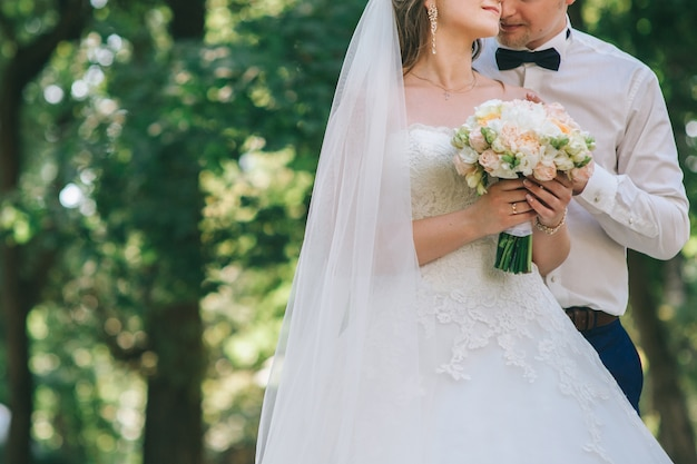 Loving couple holding hands with rings against wedding dress Premium Photo