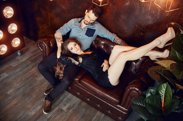 Loving couple hugging on the couch against the bright lights of lamps. passion and tenderness, man and woman love each other. woman hugging a man Premium Photo