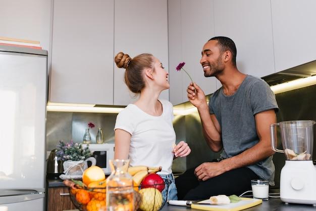 キッチンでいちゃつくtシャツの愛情のあるカップル。夫は彼の妻に美しい花を与えます。幸せそうな顔、素敵な贈り物、健康的な食事、幸せなペア。 無料写真