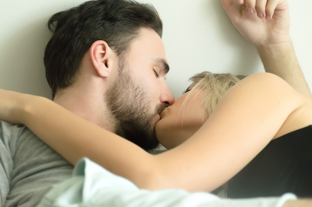 Loving Couple Kissing In Bed Happy Couple Lying Together In Bed