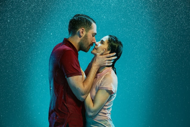 La coppia di innamorati che si baciano sotto la pioggia su uno sfondo turchese Foto Gratuite