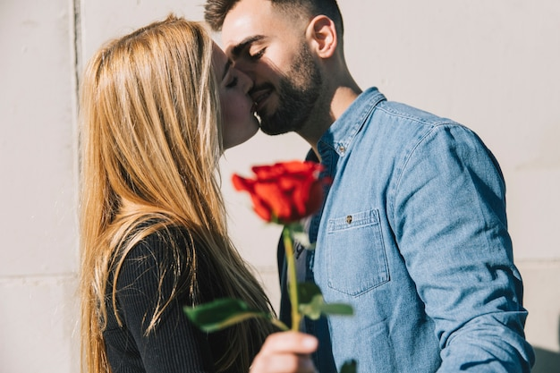 Loving couple kissing with rose in hand Free Photo