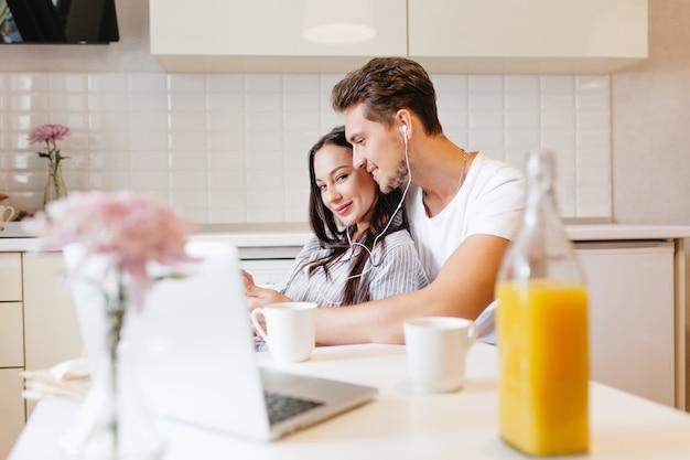 居心地の良いキッチンで朝食時に一緒に音楽を聴く愛するカップル 無料写真
