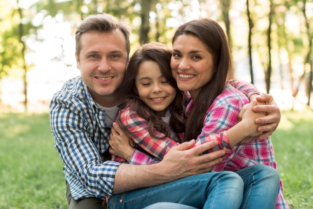Loving couple looking at camera hugging their daughter in park Free Photo