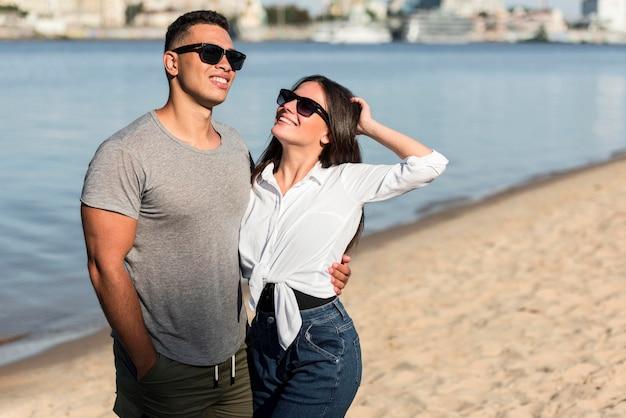 Влюбленная пара позирует вместе на пляже Бесплатные Фотографии