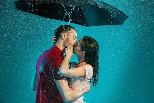 La coppia di innamorati sotto la pioggia con l'ombrello su uno sfondo turchese Foto Gratuite