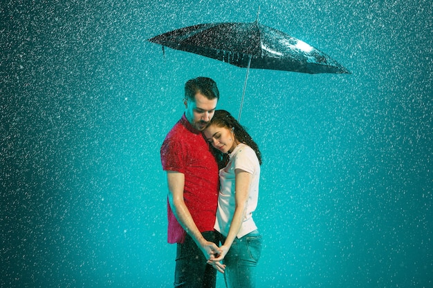 The loving couple in the rain with umbrella on a turquoise background Free Photo