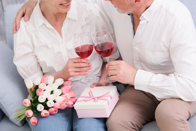 Loving couple sitting on sofa with wine glasses; gift box and bouquet of tulip flowers Free Photo
