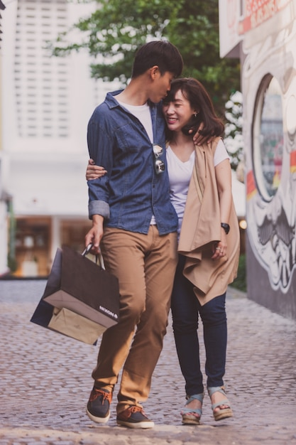 Loving couple strolling with shopping bags Free Photo