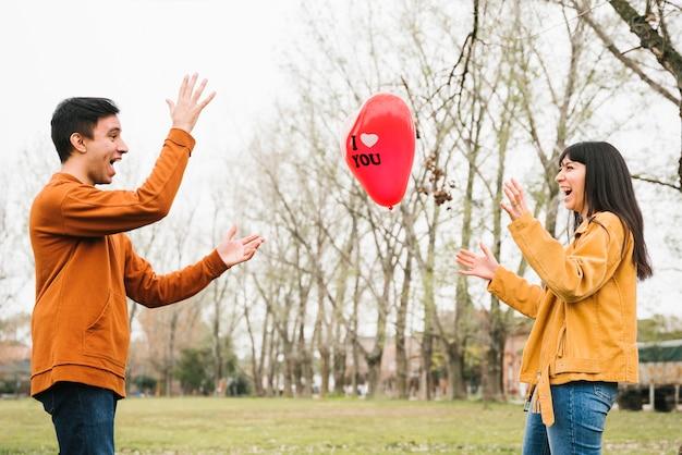 Loving couple throwing balloon outdoors Free Photo