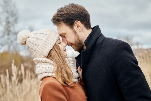 Loving couple walking in park in autumn hugs and kisses. Premium Photo