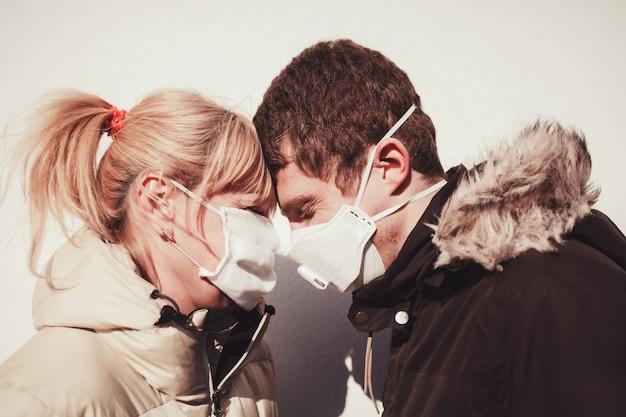 保護フェイスマスクを身に着けている愛情のあるカップル Premium写真