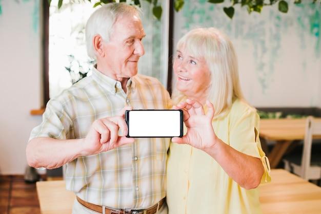 Loving elderly couple showing smartphone to camera Free Photo
