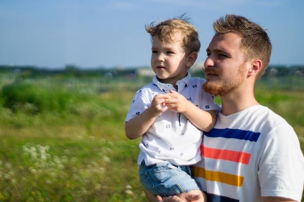 Любящая семья. отец и его сын мальчик играют и обнимаются на открытом воздухе. счастливый папа и сын на открытом воздухе. концепция дня отца. Premium Фотографии
