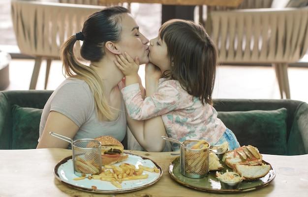 愛する家族。カフェ、家族、栄養の概念でファーストフードを食べるかわいい娘を持つお母さん 無料写真