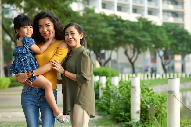 Loving family of three posing for photography Free Photo
