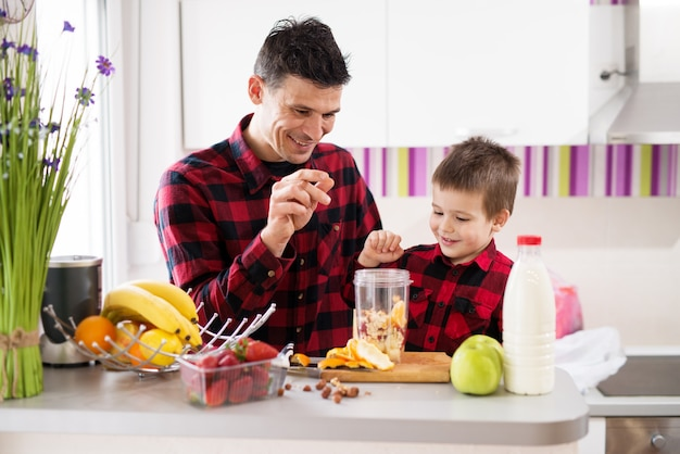 Loving father and son in same shirt are making a smoothie on the kitchen counter filled with fruits. Premium Photo